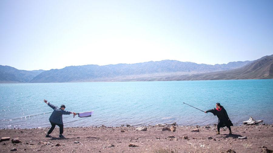 Men fishing in lake against clear sky