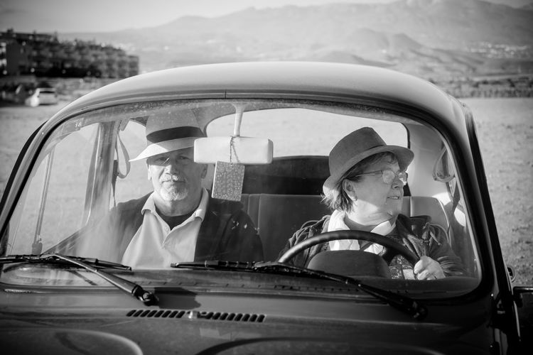 Couple Sitting In Car Against Mountains
