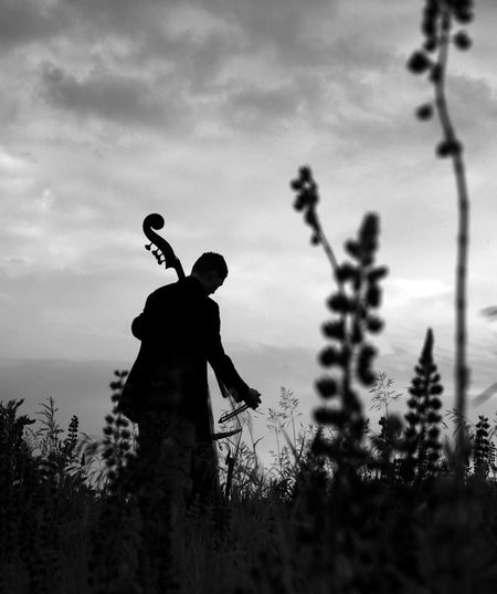 Silhouette Man Playing Violin While Standing On Field Against Sky