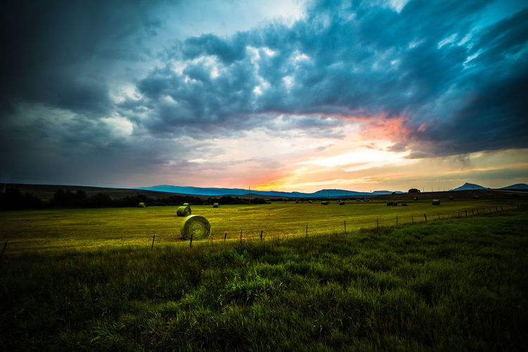 A Jolly Rancher Sunset Breaking Through the Clouds After a Storm Over a Pastoral Field Full of Freshly Rolled Hay Bales - Somewhere in the Heartland of America. Cloud - Sky Dusk Sunset Beauty In Nature Landscape Hay Bales Rural America Rural Landscape Heartland Travel Roadtrip Vanlife Grass Field Colorful Brilliant Colorful Sky Stormy Sky Sun Breaking Through Clouds Farmland Sky Rural Scene No People Warm Colors Pastoral