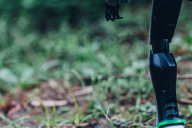 Close-up of legs of robot standing on field - futuristic sustainability / coexist tech and nature