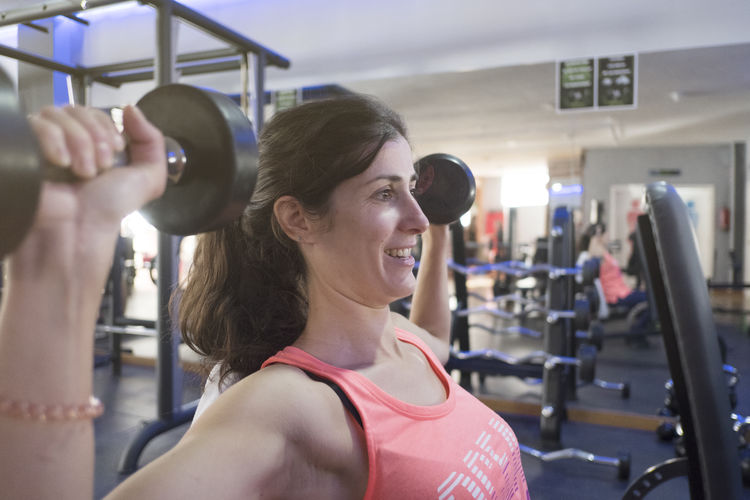 Side view of woman lifting dumbbells in gym