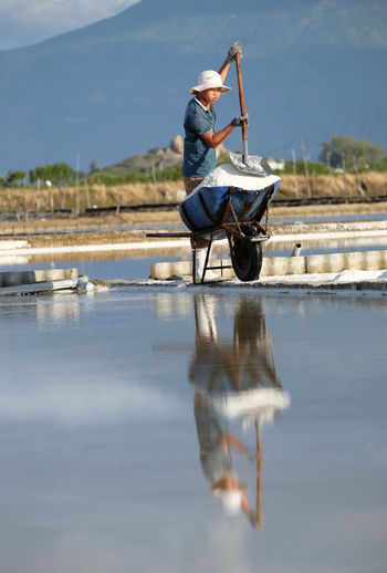 Reflection of young man working against sky