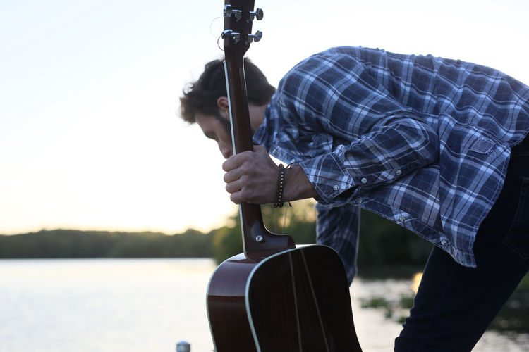 Close-up Day Guitar Holding Human Hand Men Nature Outdoors People Real People Sky Standing Sunset Two People Weapon Young Adult