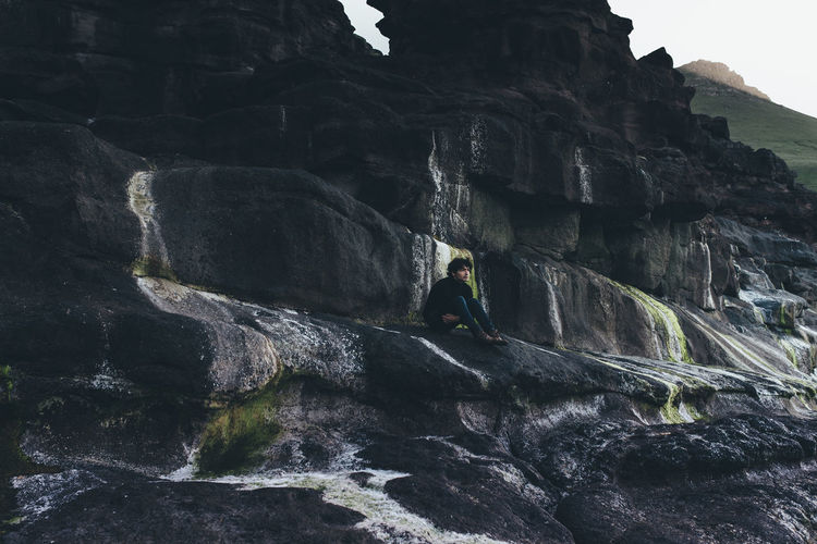 Scenic view of man sitting by cliffs