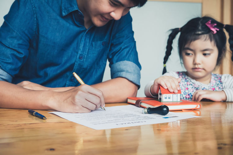 Girl Looking At Father Signing On Paper