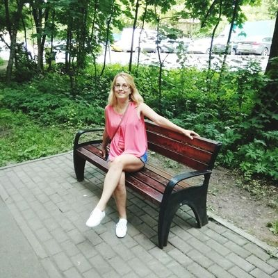 Young Women Tree Blond Hair Full Length Portrait Smiling Sitting Looking At Camera Legs Crossed At Knee Seat