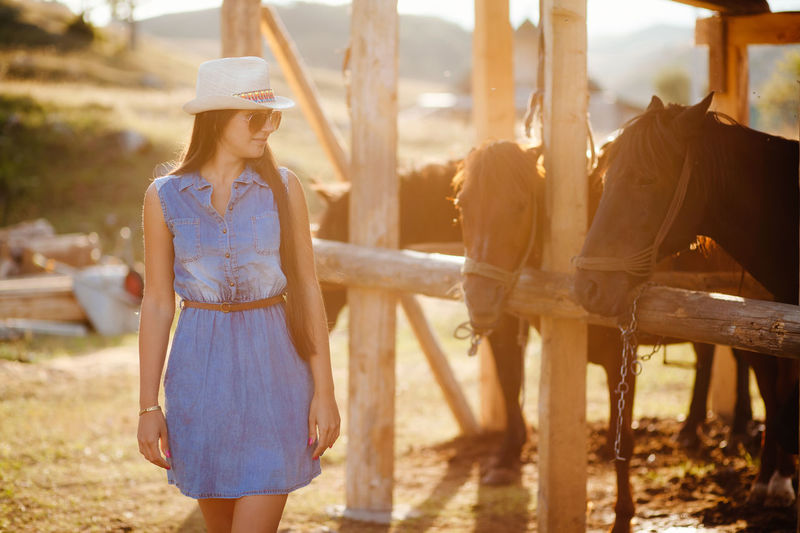 woman stand with horses on ranch. ranch life in summer. Cowboy EyeEm Best Shots Ranch Life Brunette Countryside Day Friendship Horse Leisure Activity Lifestyles Nature Outdoors Real People Standing Togetherness Young Adult Young Women