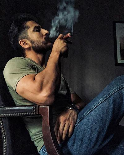 Man smoking cigar while sitting on chair