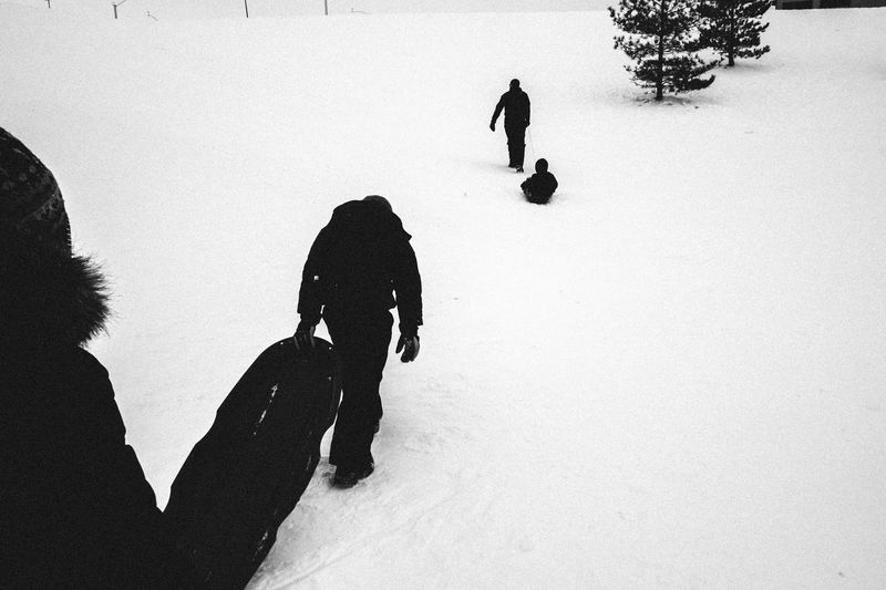 Rear View Of People Walking With Sleds On Snow Covered Field