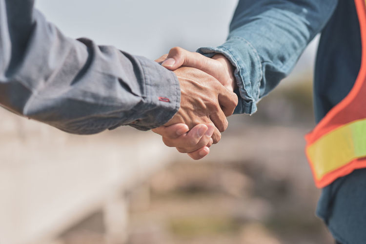 Close-up of coworkers shaking hands at construction site