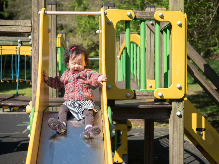 Baby girl playing on slide at playground
