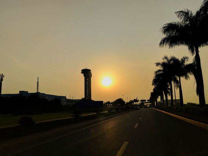 The sun rise over the approach to Kempagowda International Airport in Bangalore Silhouette Travel Destinations Road Vacations No People Outdoors Tree Sky Airport Sunrise