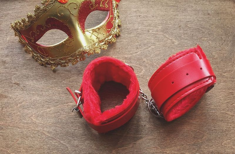 Red handcuffs Bdsmlifestyle Erotic_photo Mask - Disguise Handcuffs  Red Still Life High Angle View No People Jewelry Positive Emotion Close-up Emotion Personal Accessory Fashion Table
