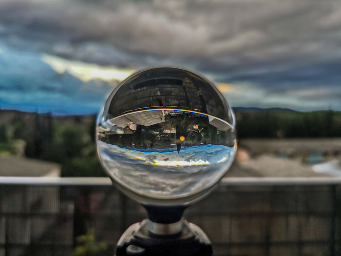 Close-up of crystal ball on glass against sky