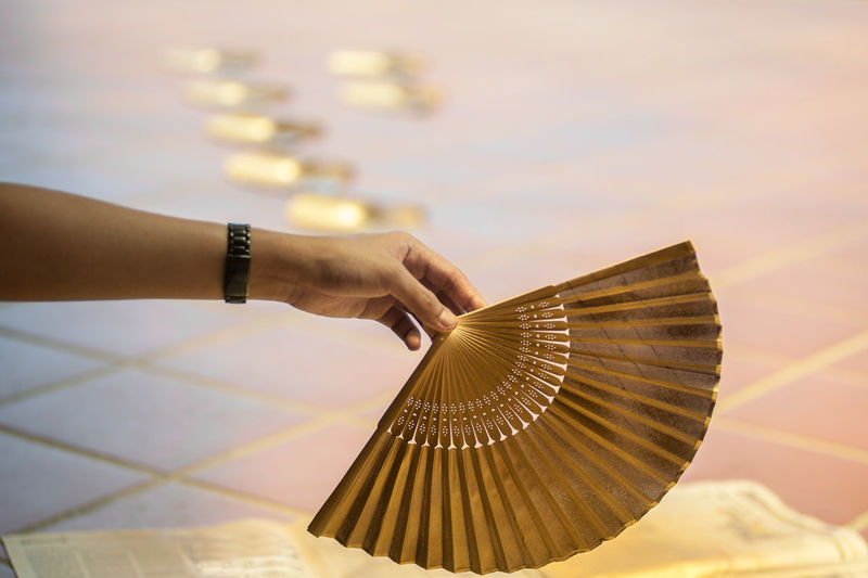 Cropped hand holding folding fan against tiled floor