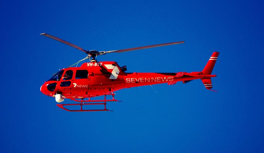 Channel 7 news chopper in clear blue sky. Blue CH7 News Chopper Clear Sky Day Helicopter Low Angle View Mode Of Transport News Chopper Outdoors Red