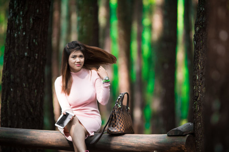Portrait of beautiful woman sitting on fallen tree at forest