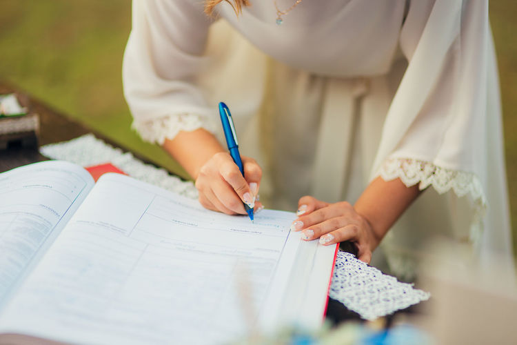 Midsection of woman writing in book on table