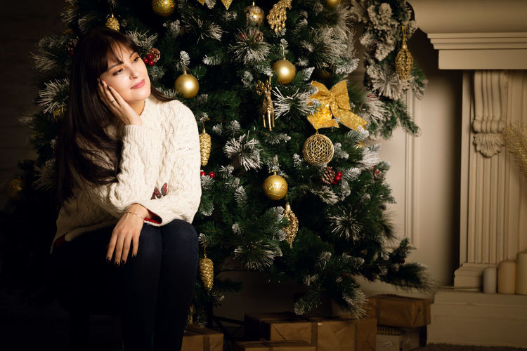 Young woman with christmas tree at home