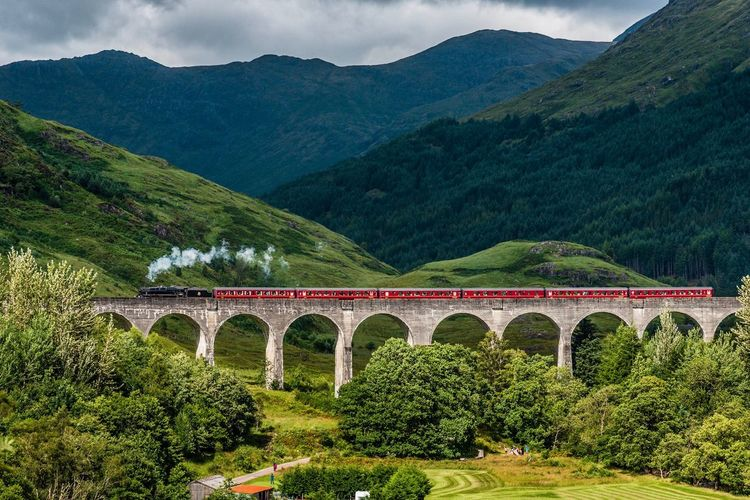‪The Jacobite steam train 🚂 crossing the 21-arched Glenfinnan viaduct (a location made famous in the Harry Potter films, where it made its way to Hogwarts).‬ Glenfinnan Viaduct Scotland Train Steam Train Plant Mountain Built Structure Architecture Bridge Nature Bridge - Man Made Structure Mountain Range Beauty In Nature Transportation Scenics - Nature