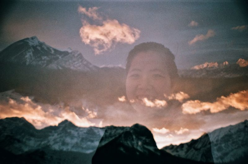 Portrait of smiling man against mountains during sunset