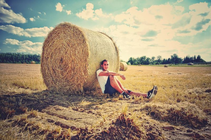Full length of man sitting by hay bale on field