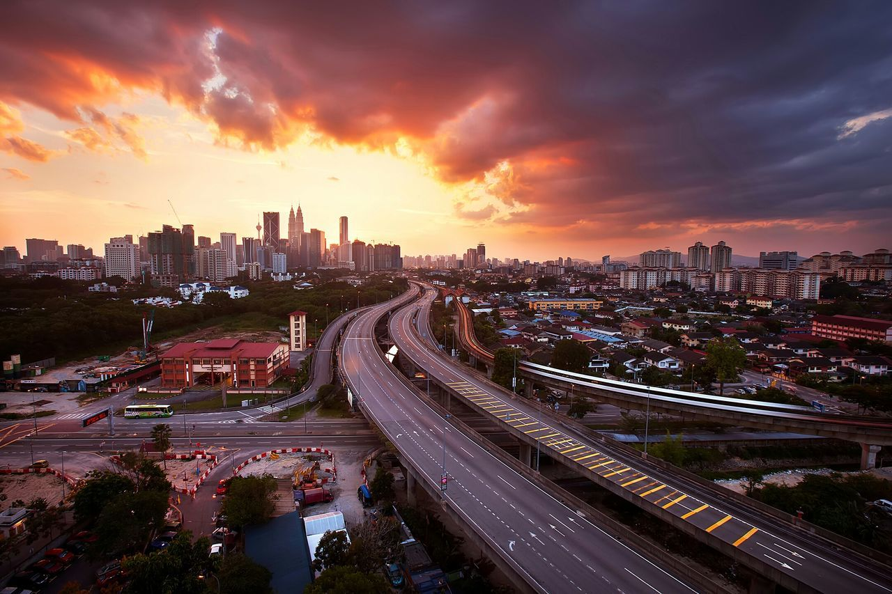 High angle view of multiple lane highway amidst buildings against cloudy sky