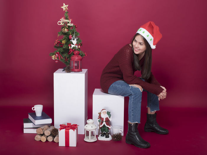 Full Length Of Young Woman Sitting By Christmas Tree And Decorations Against Red Background