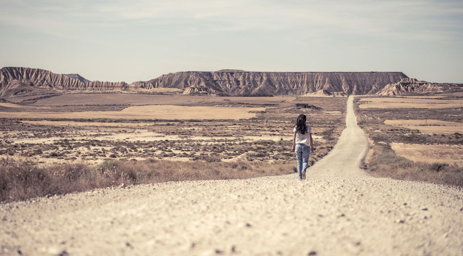 Rear View Of Woman Walking On Dirt Road At Desert Against Sky