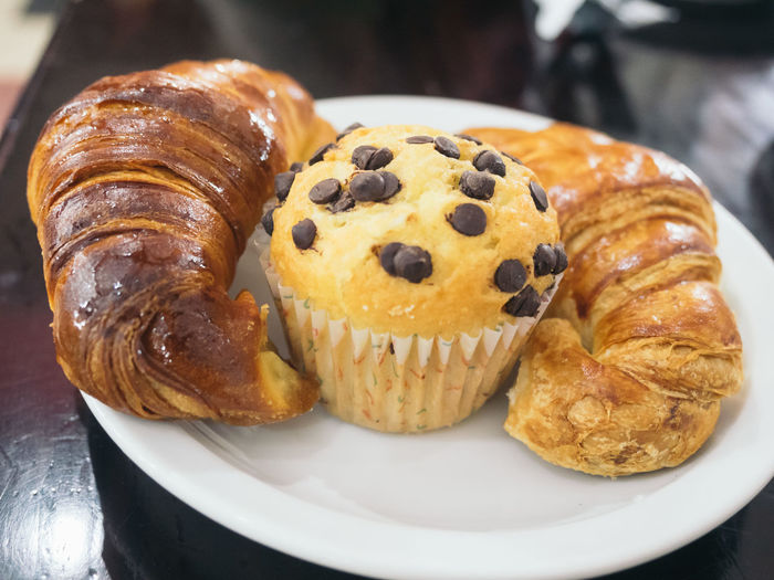 Close-up of muffin and croissants in plate on table