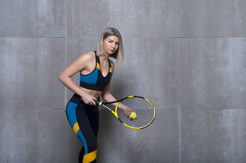 Woman playing tennis while standing against wall
