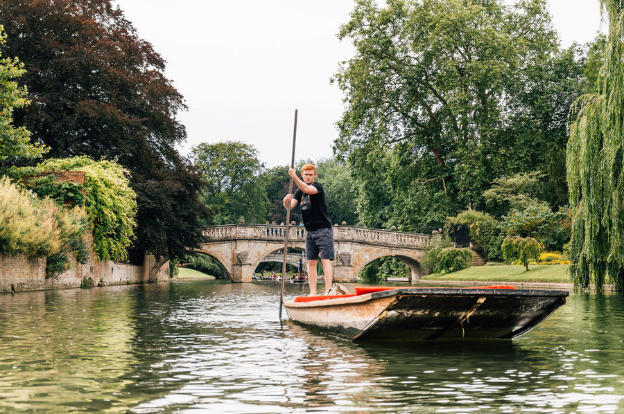 Young man punting in the river in Cambridge Boat Boats Cambridge Canal Casual Clothing Day Green Color Leisure Activity Lifestyles Nature Outdoors Punting Reflection Rippled River Sailing Sky Sport Student Tranquil Scene Tranquility Tree University Water Waterfront