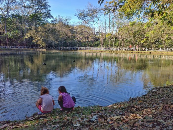 Children sitting by lake against sky