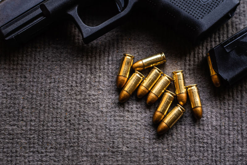 High angle view of golden bullets and gun on textile
