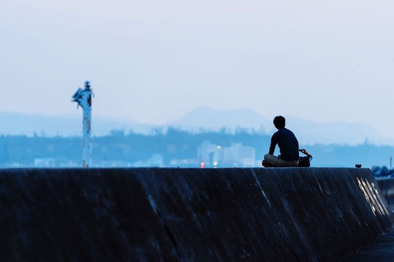 Rear view of man sitting on retaining wall against clear sky