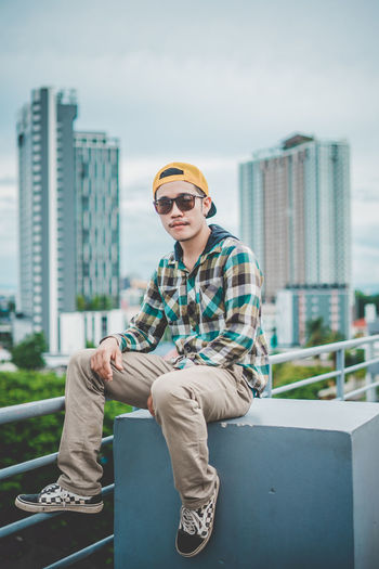 Portrait of young man wearing sunglasses and cap while sitting in city
