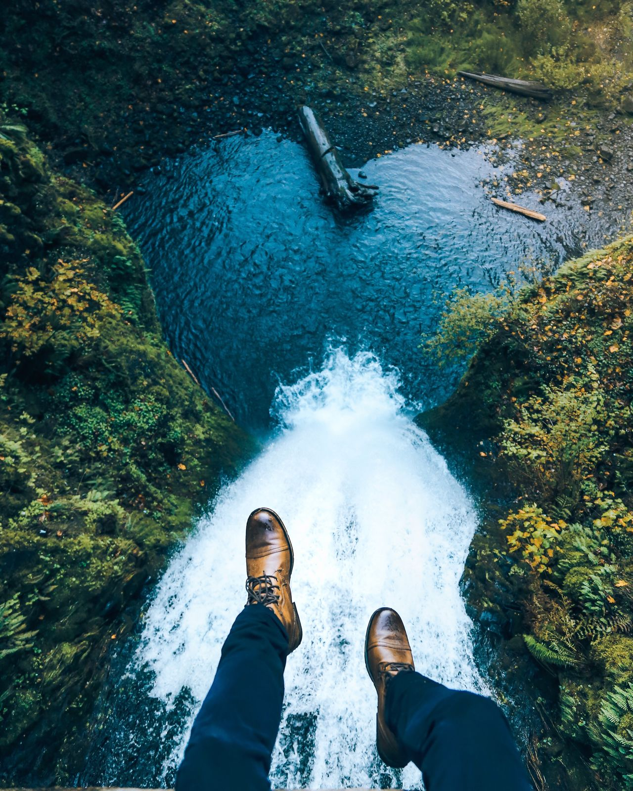 Low section of man sitting above river