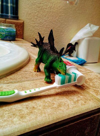 Even dinosaurs brush their teeth Dental Hygiene Dental Hygiene Concept Toy Dinosaurs Toothbrush Dinosaur Figurine  Toy Dinosaur Close-up