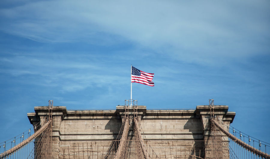 Low Angle View Of American Flag On Brooklyn Bridge Against Sky