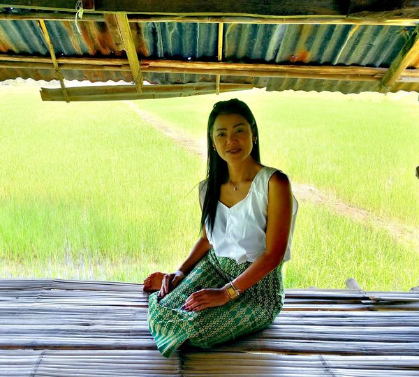 Portrait Of Smiling Woman Sitting In Hut