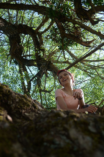 Low angle view of woman sitting on tree trunk