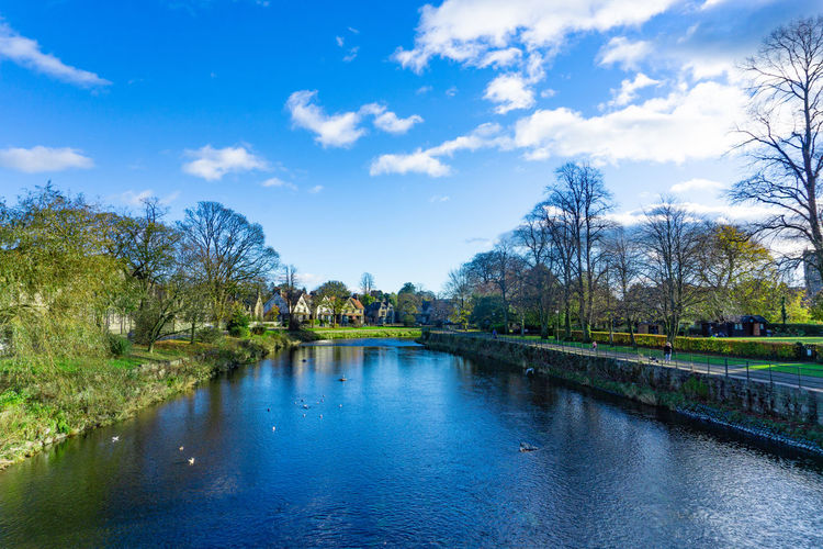 Cityscape of River Kent in Kendal, Cumbria, England in cloudy blue sky day Water Tree Sky Plant Cloud - Sky Waterfront Nature Scenics - Nature Beauty In Nature No People Reflection Tranquil Scene Architecture Tranquility Built Structure Day Lake Blue Outdoors
