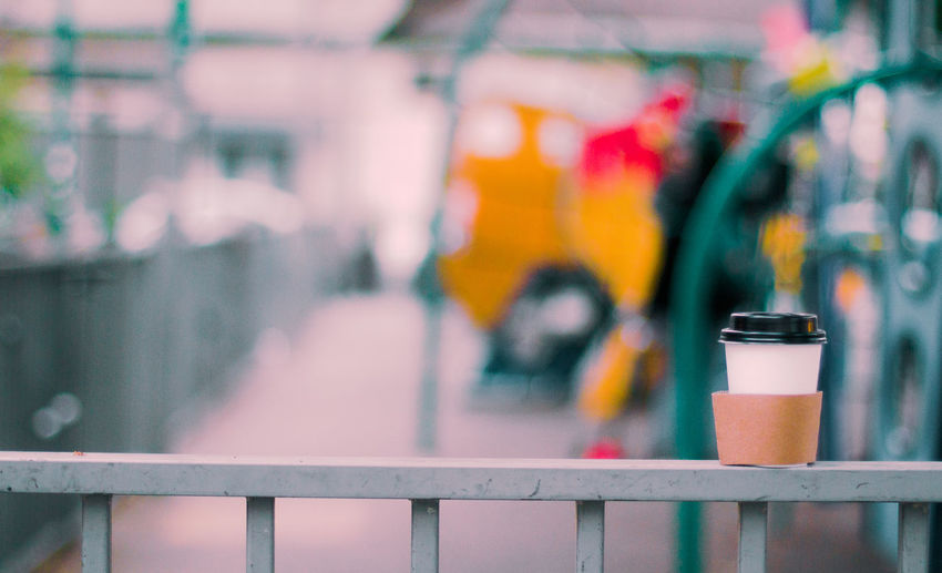 Close-up of metal fence against blurred background  paper coffe cup resting.