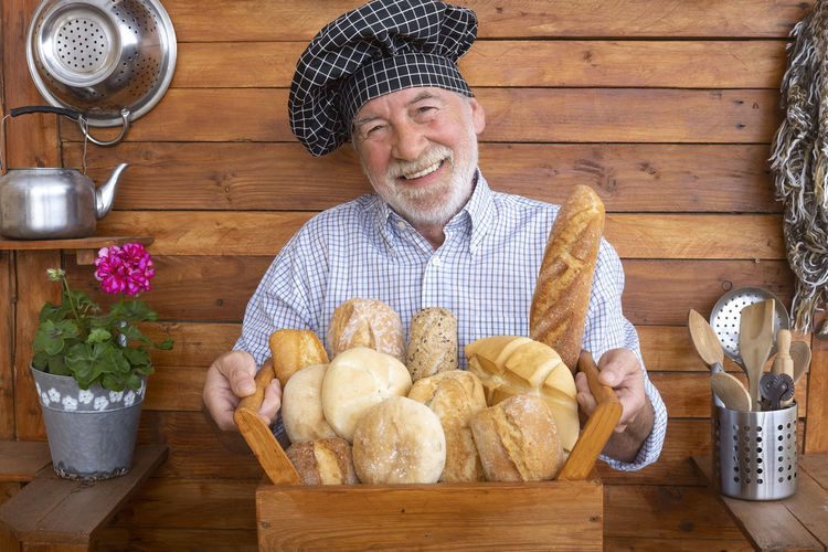 Portrait of man holding bread in container