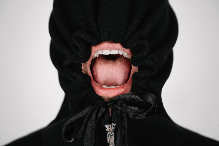 Close-up of person wearing mask and hood against white background