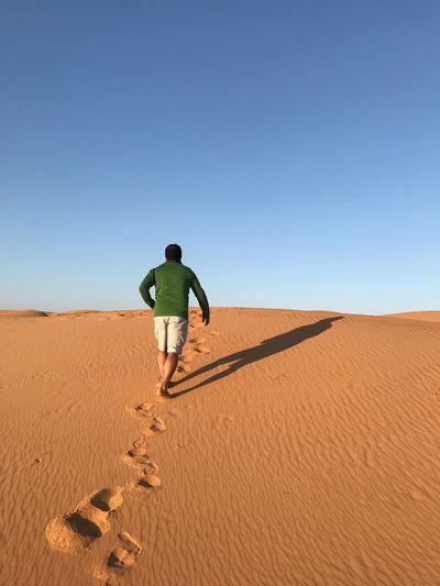 Rear View Of Man Walking On Desert Against Clear Sky