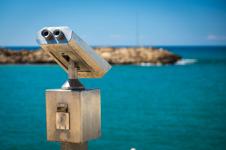 Close-up metal binoculars for public use with views of the beautiful port and sea