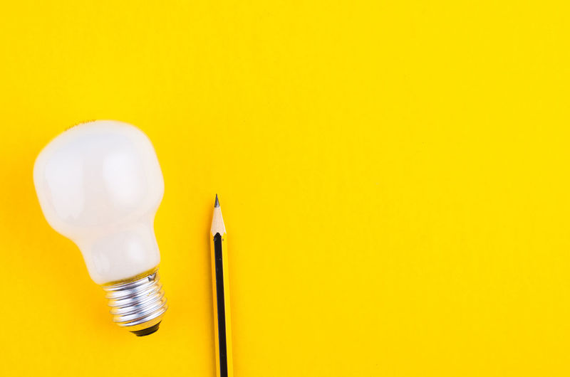 pencil and bulb over yellow background Yellow Light Bulb Copy Space Indoors  Studio Shot Colored Background Lighting Equipment No People Close-up Yellow Background Illuminated Still Life Single Object Cut Out Two Objects Electricity  Creativity Vibrant Color Directly Above Energy Efficient Electric Lamp