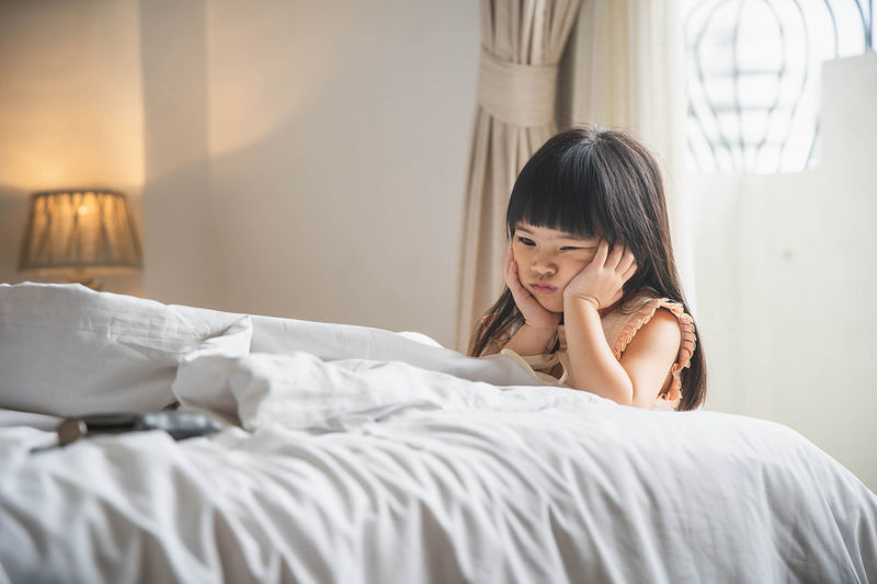 Woman looking away while relaxing on bed at home